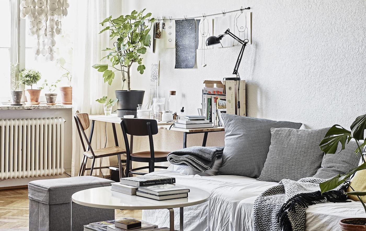 Salon avec canapé et bureau dans des couleurs neutres.