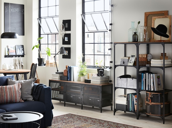 Salon avec étagères et un banc TV en métal noir et bois dans un atelier rénové.