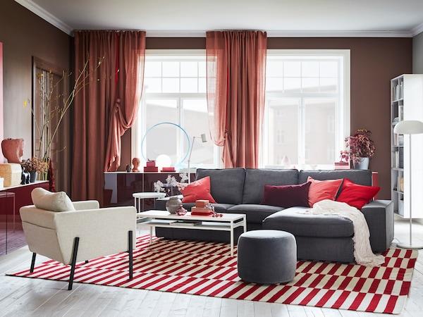 Salón con grandes ventanas, cortinas naranjas, alfombra a rayas y sofá gris.