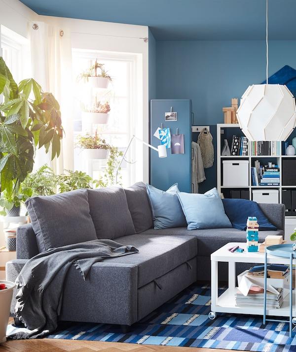 Salón con sofá de esquina en el centro, rodeado de grandes estanterías llenas de cosas, ventanales y varias plantas.