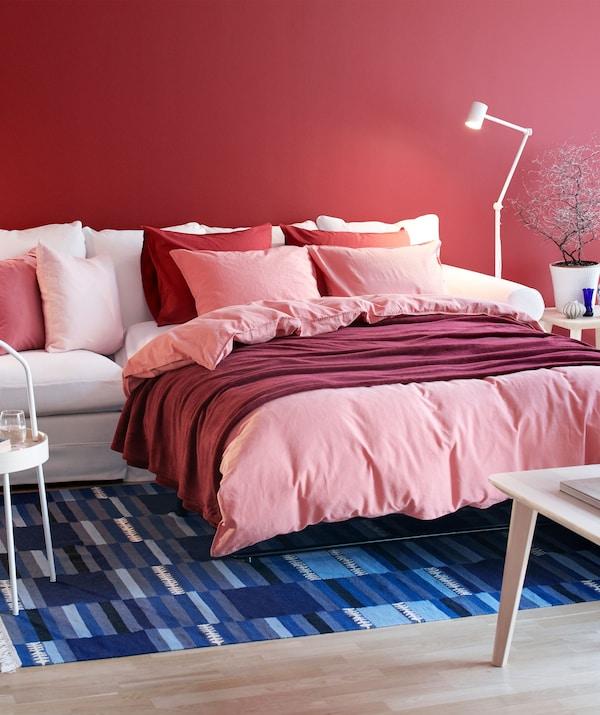 Salón con sofá GRÖNLID extendido para convertirse en una cama de matrimonio, perfectamente hecha, con varias capas de textiles y cojines mullidos.