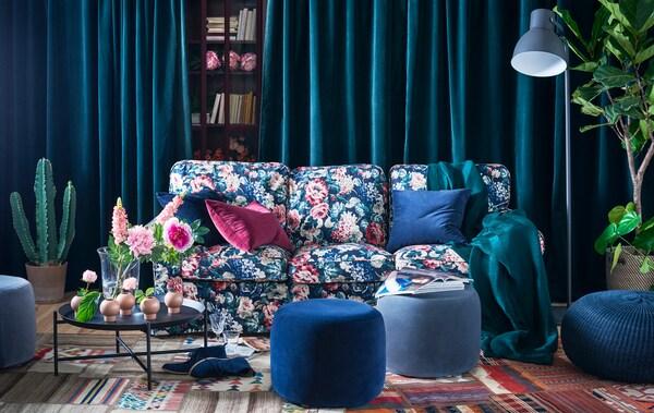 Salón con un sofá con estampado floral, reposapiés azul y verde y cortinas.
