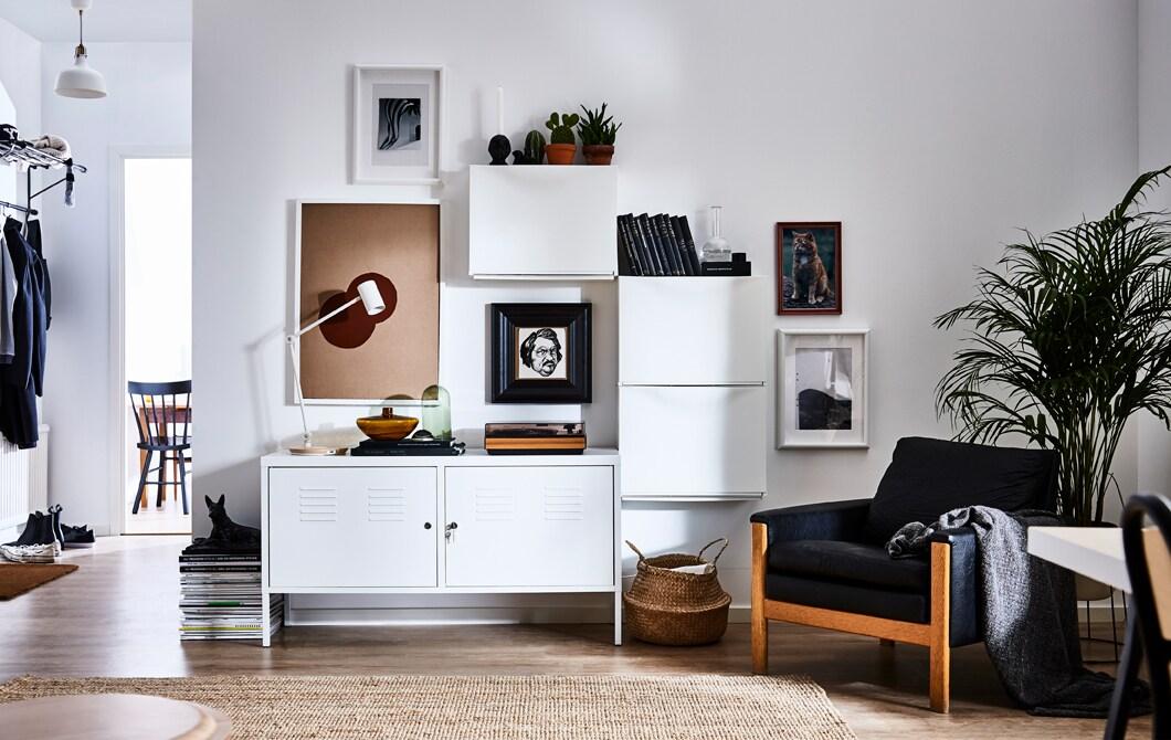 Salon d'allure moderne comportant trois range-chaussures TRONES placés au mur, à proximité d'un rangement. L'ensemble devient le point central de la pièce et procure un espace rangement fermé intéressant.