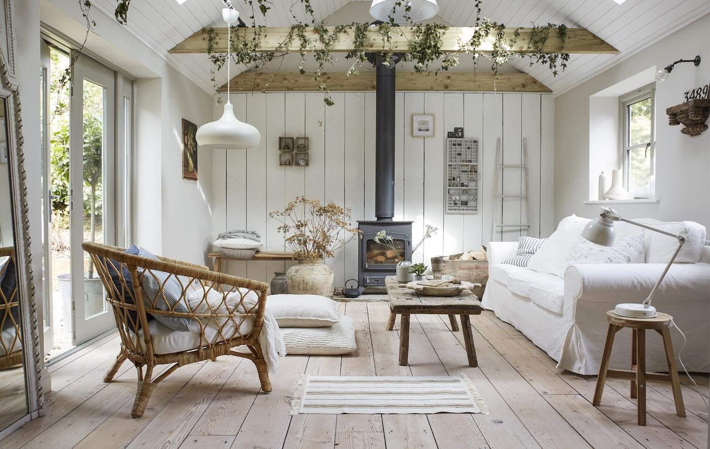 Salon de couleur claire décoré d'un canapé blanc et d'une chaise en osier, avec poutres et planchers en bois.