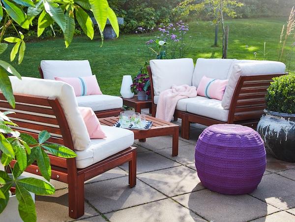 Salon de jardin 4 pièces et table en acacia, coussins d'extérieur beiges, pouf violet, plaid et coussins roses.
