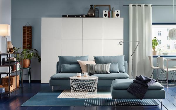 Salon de taille moyenne avec canapé 3 place et repose-pieds turquoise, une table avec rangement intégré blanche et une grande combinaison de rangement en gris-turquoise.
