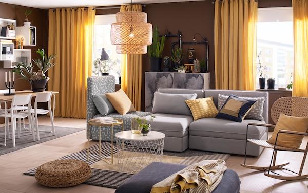 Salon de taille moyenne avec combinaison 3 places en gris uni et à motif noir/beige, qui peut être converti en lit. Assorti à une table de rangement blanche et un fauteuil à bascule contemporain en rotin tissé main.