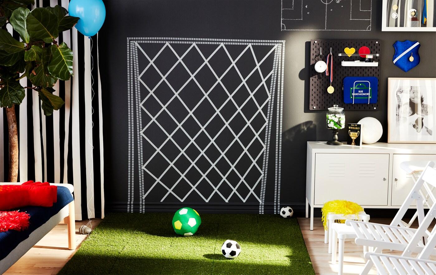 Salón decorado para imitar a un campo de fútbol con césped artificial y portería pintada en la pared