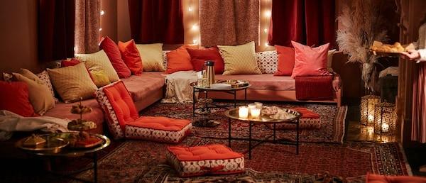 salon décoré avec un style oriental, des grandes banquettes sont recouvertes avec des coussins rouges, roses et dorés.
