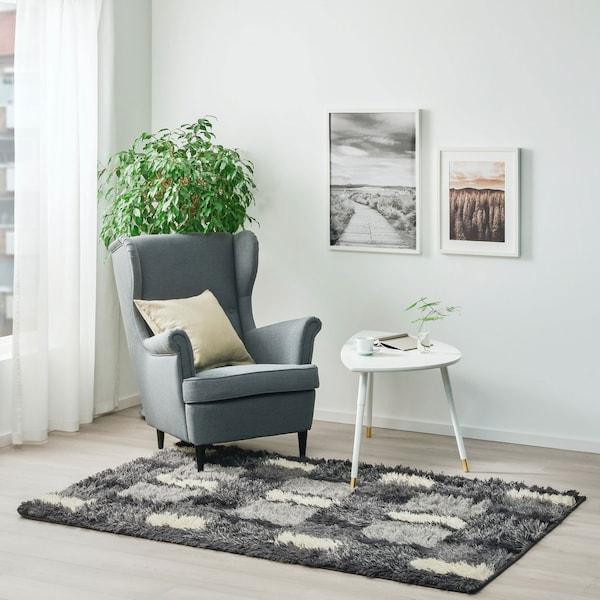 Salon éclairé avec tapis gris à poils longs et fauteuil gris