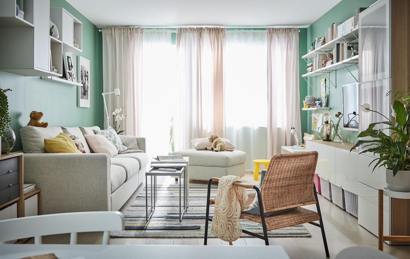 Salon éclairé par de grandes fenêtres devant lesquelles sont tirés des rideaux légers. Canapé, sièges, rangements ouverts le long des murs.