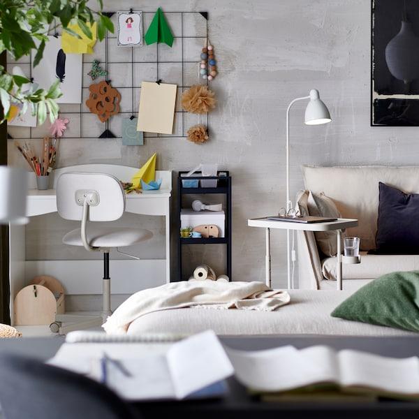 Salón en tonos neutros con un escritorio blanco y una silla de trabajo en la esquina. Hay un tablero de notas en la pared que hay encima.