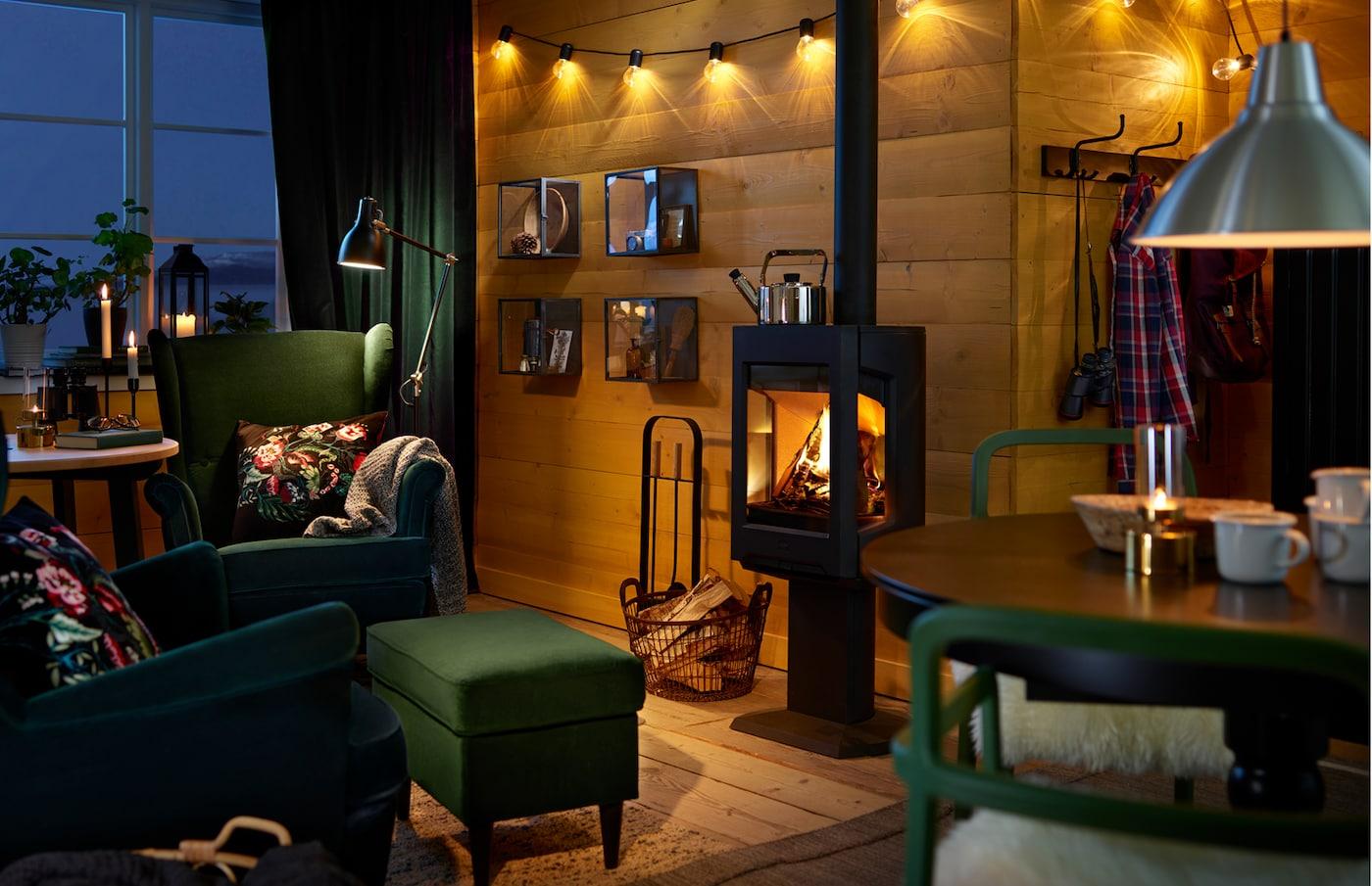 Salon meublé en vert et bleu, murs en planches et luminaires chaleureux