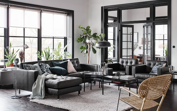 Salon noir, beige et blanc avec un canapé et méridienne en cuir noir et deux fauteuils côte à côte.