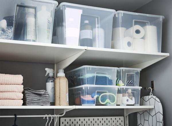 SAMLA Boxen mit Deckel transparent, gefüllt mit Waschutensilien und mehr, gestapelt auf Wandregalen.