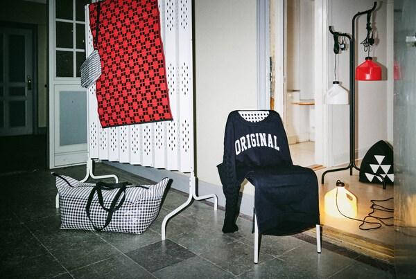 SAMMANKOPPLA bútorok, egy széken kék pulóverre emlékeztető huzat, a földön lámpa.