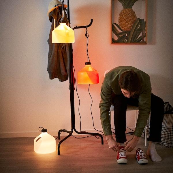 SAMMANKOPPLA fogasra lámpák akasztva, mellettük egy fiú a cipőjét veszi fel.