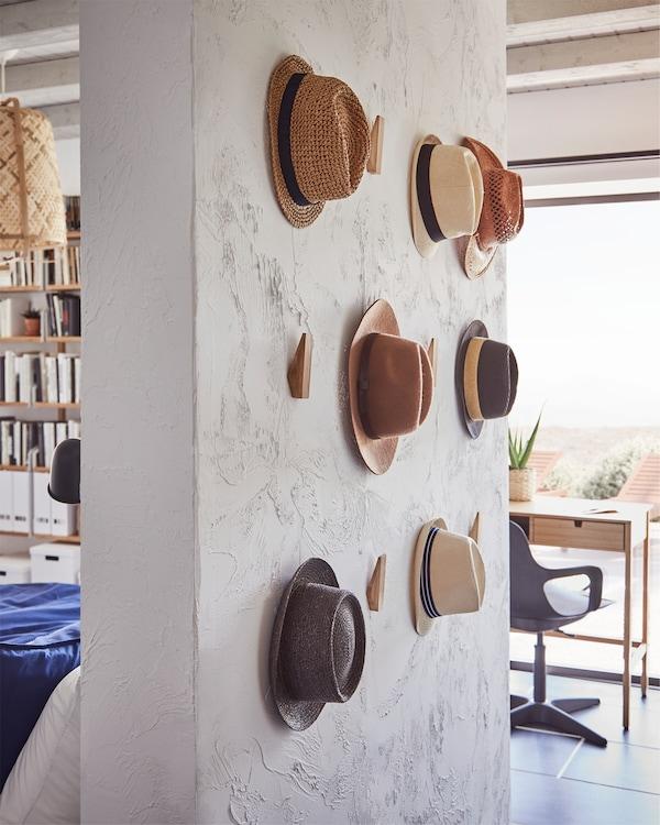 Samostojeći zid s SKUGGIS kukicama od bambusa postavljenim na različitim visinama i šeširi koji vise s nekih od njih.