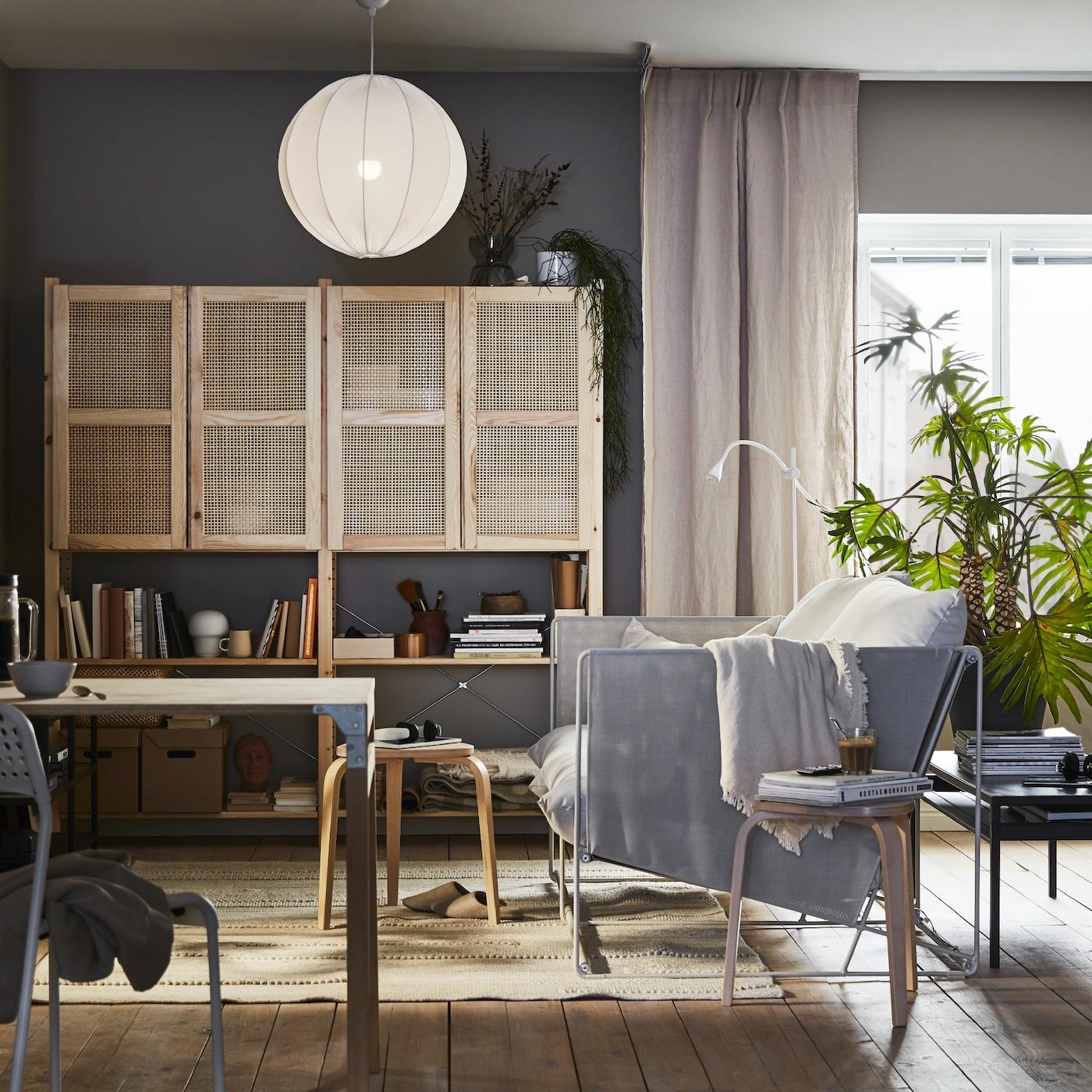 Sanft erleuchtetes Wohnzimmer, das für verschiedene Aktivitäten ausgelegt ist: Entspannung, Arbeit, Zimmerpflanzen und Aufbewahrungen sind zu sehen.