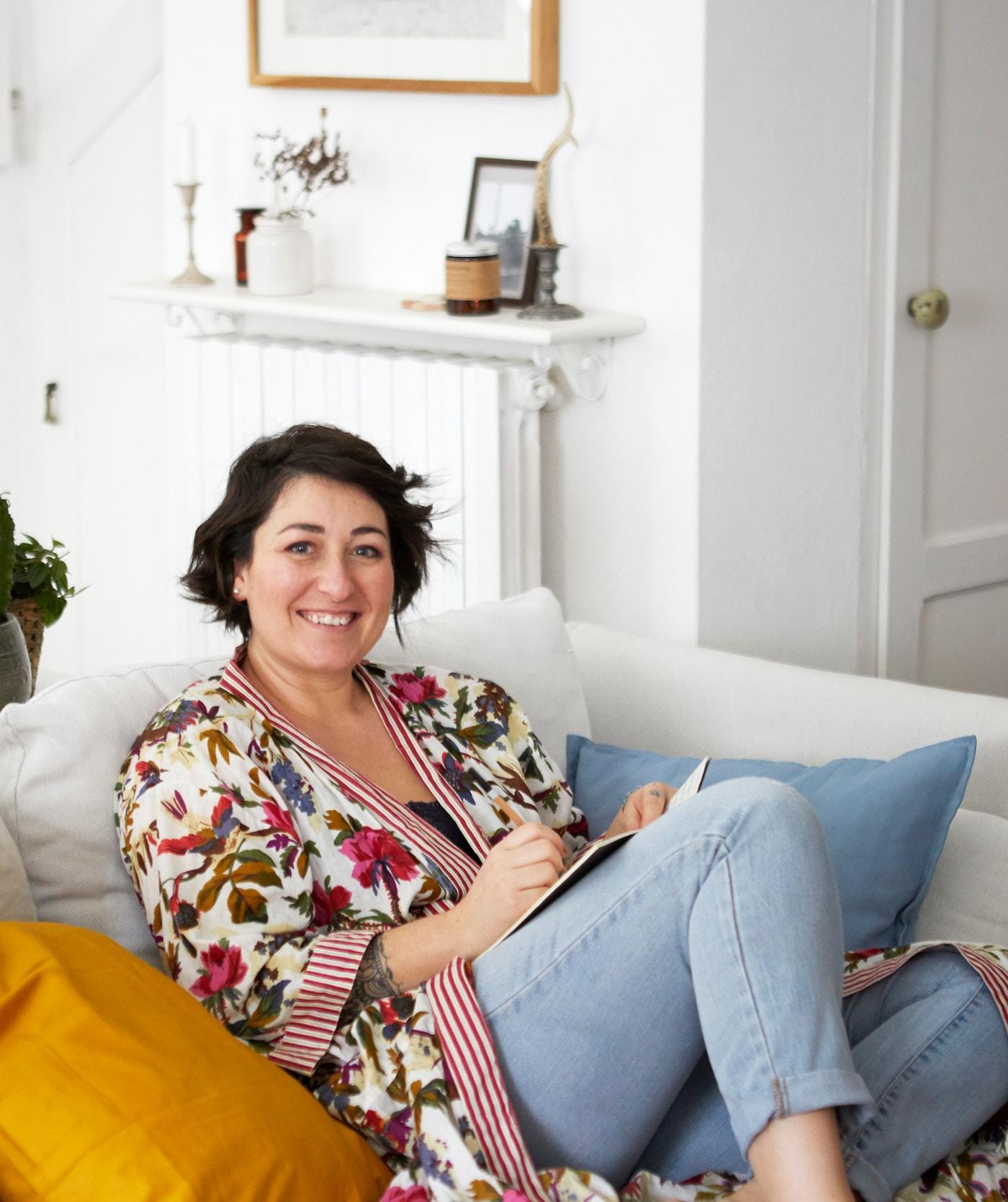 Sarah assise sur un canapé blanc dans une pièce blanche.