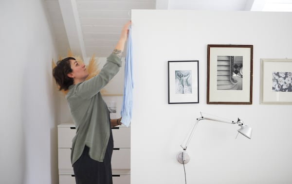 Sarah hängt hinter einer weißen Wand, an der Schwarzweißfotos zu sehen sind, ein Hemd auf.