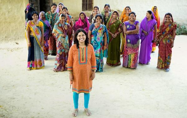 舗装されていない道に立っている、カラフルなロングスカートの民族衣装を着た15人ほどの笑顔の女性グループ