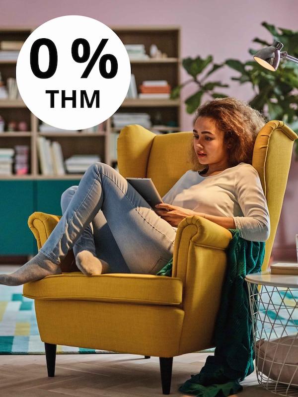 Sárga STRANDMON fotelben ül egy nő és olvas.