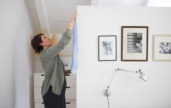 سارة تقوم بتعليق قميص خلف حائط أبيض مزين بصور أبيض وأسود.