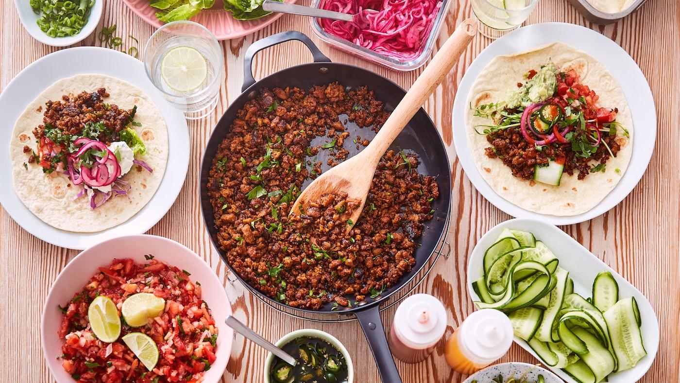 Sartén con carne picada vegetal HJÄLTEROLL preparada para tacos, con platos y cuencos con pico de gallo y tortillas al lado.