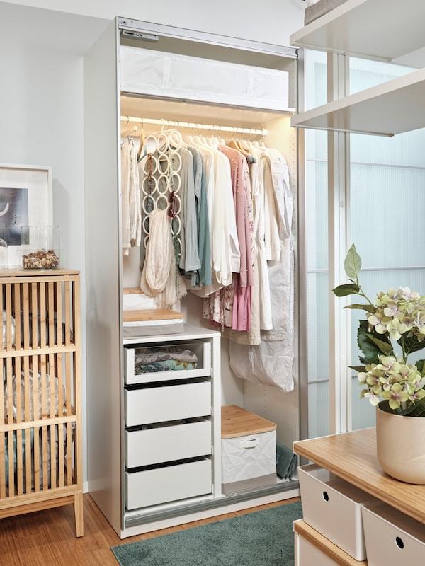 Šatní skříň PAX s posuvnými dveřmi NYKIRKE, uvnitř jsou čtyři zásuvky, tři krabice RABBLA a spousta ramínek s dámským oblečením. Vlevo je část bambusové skříně NORDKISA. V popředí je vidět část úložné sestavy ELVARLI.
