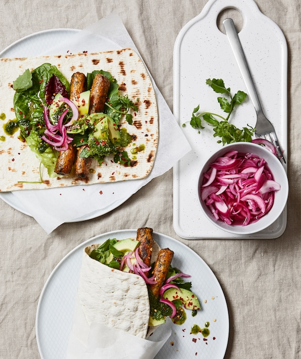 Sausages and salad in wraps on white plates.