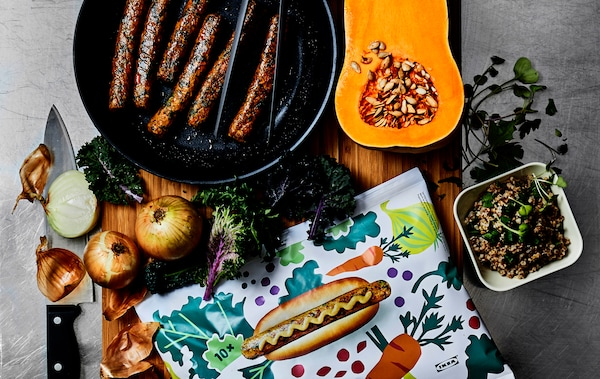 Sausages in a pan, vegetables and patterned hot dog packaging on a wooden board.