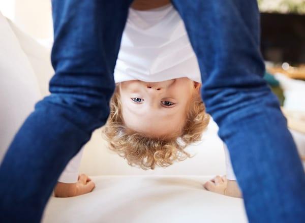 صبي يقف على قدميه ورجليه على صوفا بيضاءويلعب، رمزًالسلامةالمنتجات في ايكيا.