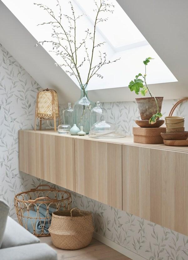 Scaffali in legno chiaro con antina appesi al muro nella parte bassa di una spiovenza. Sopra e sotto i mobili ci sono vari oggetti decorativi.