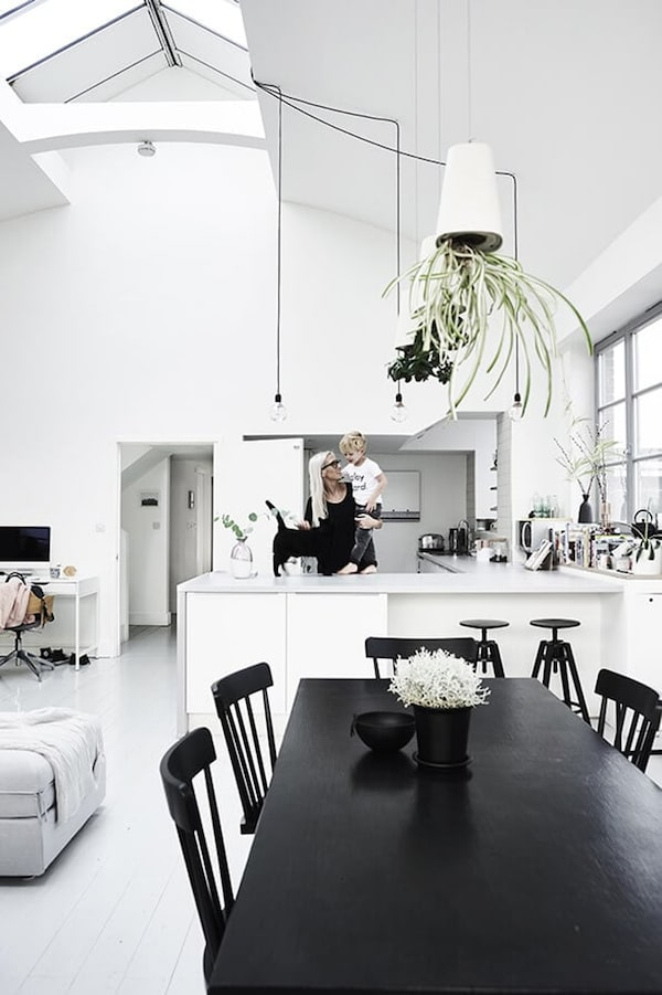 Scandinavian dining room with black dining table and chairs and white kitchen