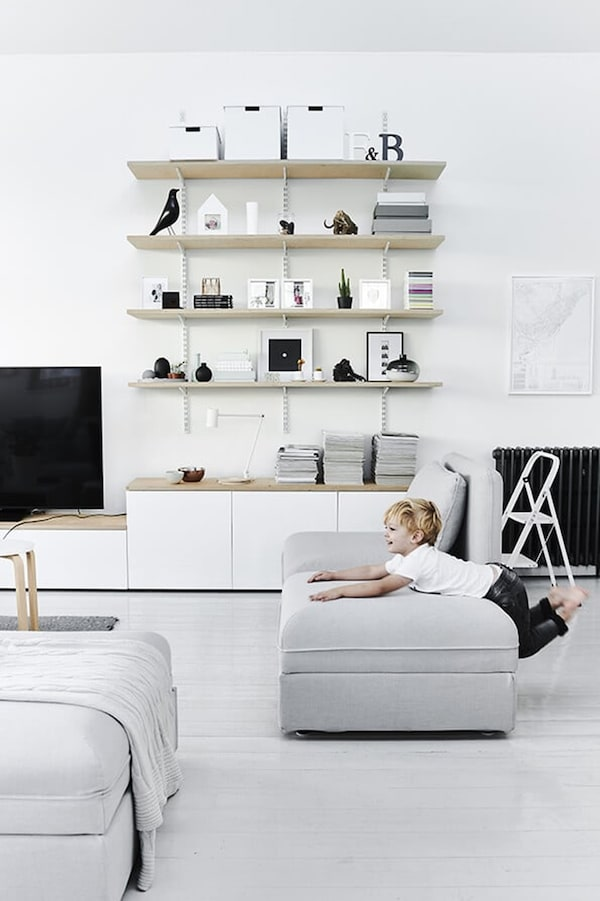 Scandinavian interior with child on light grey sofa