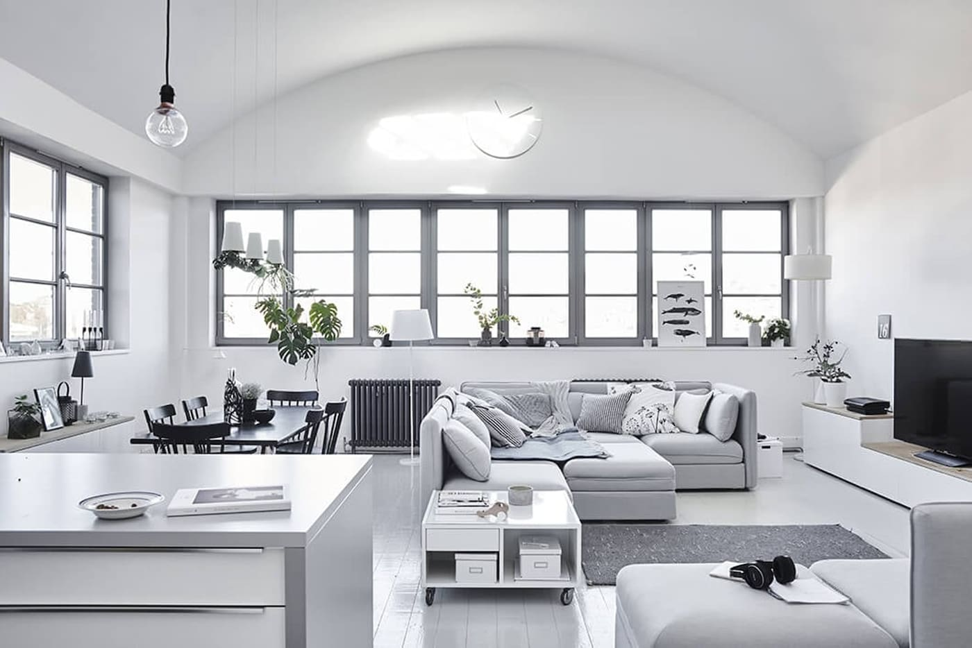 Scandinavian interior with seating area, dining table and kitchen in white and grey tones