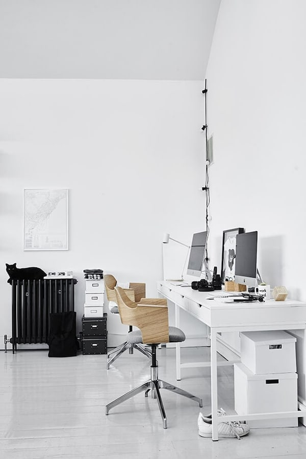 Scandinavian workspace with two screens, a white desk and two office chairs