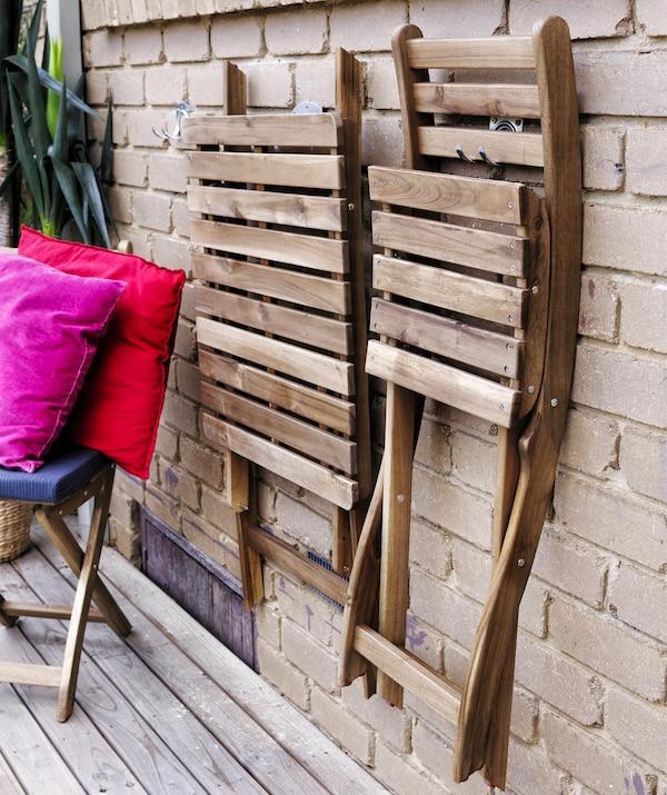 Scaune pliabile din lemn suspendate pe un perete de cărămidă.