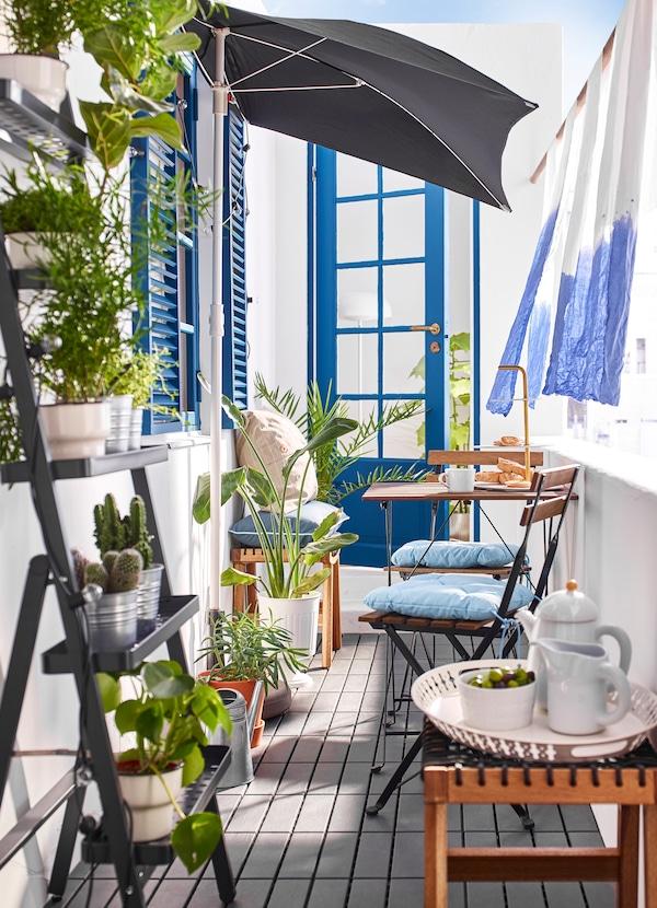 Scaune și o masă TÄRNO maro, băițuite,  într-un balcon exterior îngust.