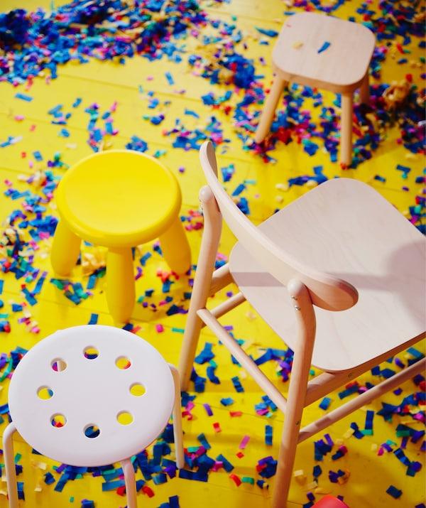 Scaunele din plastic MAMMUT și MARIUS și scaunul RÖNNINGE din lemn masiv de mesteacăn așezate pe podea, în timpul unei petreceri.