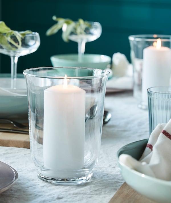 Schaffe eine gemütliche Atmosphäre am Esstisch, z. B. indem du eine duftneutrale weiße IKEA FENOMEN Blockkerze in POMP Vase/Windlicht aus Klarglas stellst.