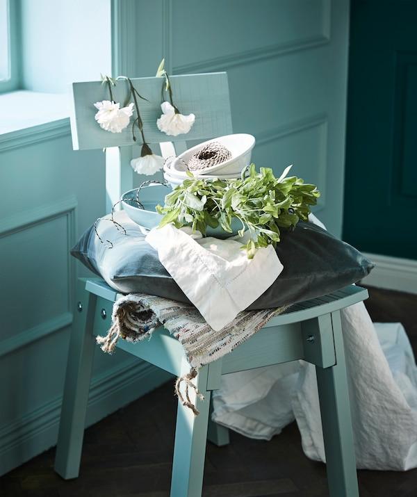 Schaffe einen sommerlich gedeckten Tisch mit verschiedenen schönen Grüntönen. Z. B. mit IKEA ENTYDIG Geschirr in Hellgrün und einem hell graugrünen INDUSTRIELL Stuhl.