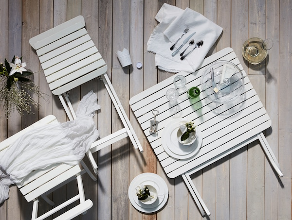 Schematic layout on a floor of a dinner kit consisting of sturdy, elegant pieces in white, complemented by white textiles.