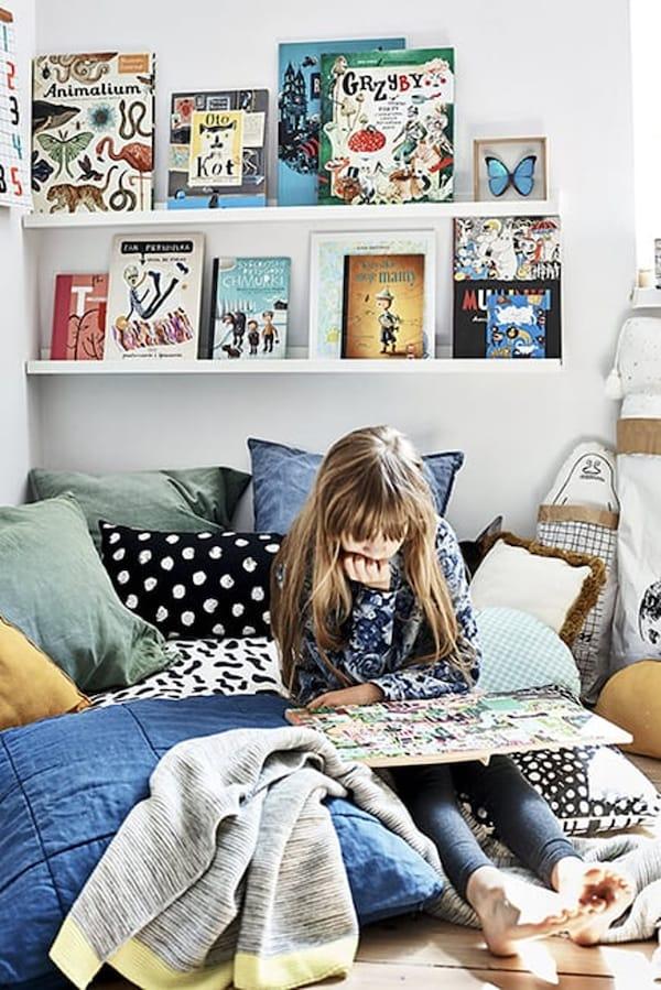 Schilderijenplanken als boekenplank aan de muur op kinderkamer Hania