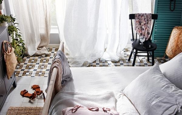 Schlaftimmer mit offenen, bodenlangen Fenstern mit dünnen Gardinen davor, die scheinbar von einer sanften Brise bewegt werden.