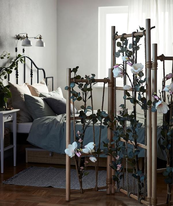 Schlafzimmer, in dem das Bett durch einen TÄNKVÄRD Raumteiler vom Rest des Raums abgetrennt wird. TÄNKVÄRD ist mit Kunstblumen geschmückt.