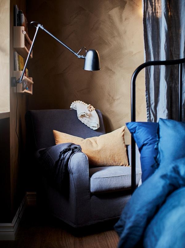 Schlafzimmer mit einem GRÖNLID Sessel in einer Ecke hinter dem Bett. Darüber ist eine Leuchte zu sehen, die an einem Regal befestigt ist.