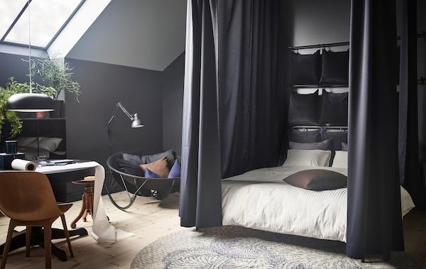 Schlafzimmer mit einem runden Tisch und einem Bett. Das Bett ist umgeben von Gardinen, die an der Decke befestigt sind. Am Bettkopf sind viele Kissen an der Wand montiert.
