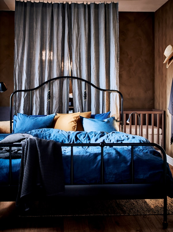 Schlafzimmer mit einem schwarzen SAGSTUA Bettgestell und hinter dem Vorhang in der Ecke ist das Babybett zu sehen.